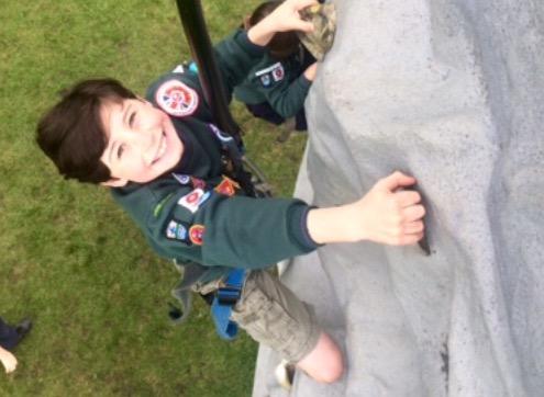 A young boy climbing a wall