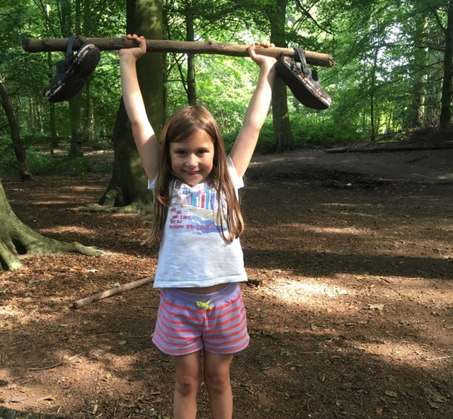 A young girl holding a stick up with her boots hanging off