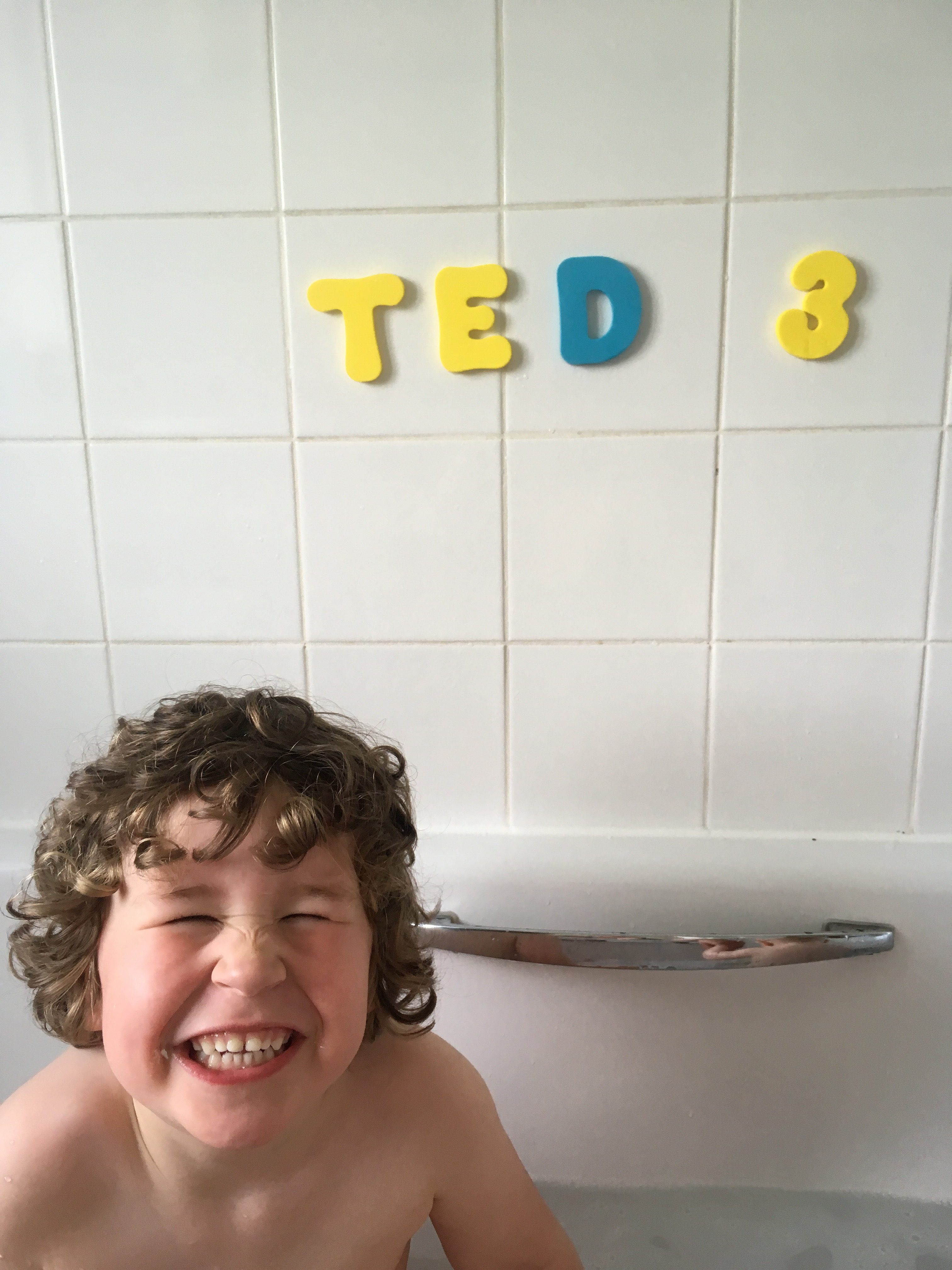 Summerborn -child smiling form a bathtub with his name spelt out on the bath tiles