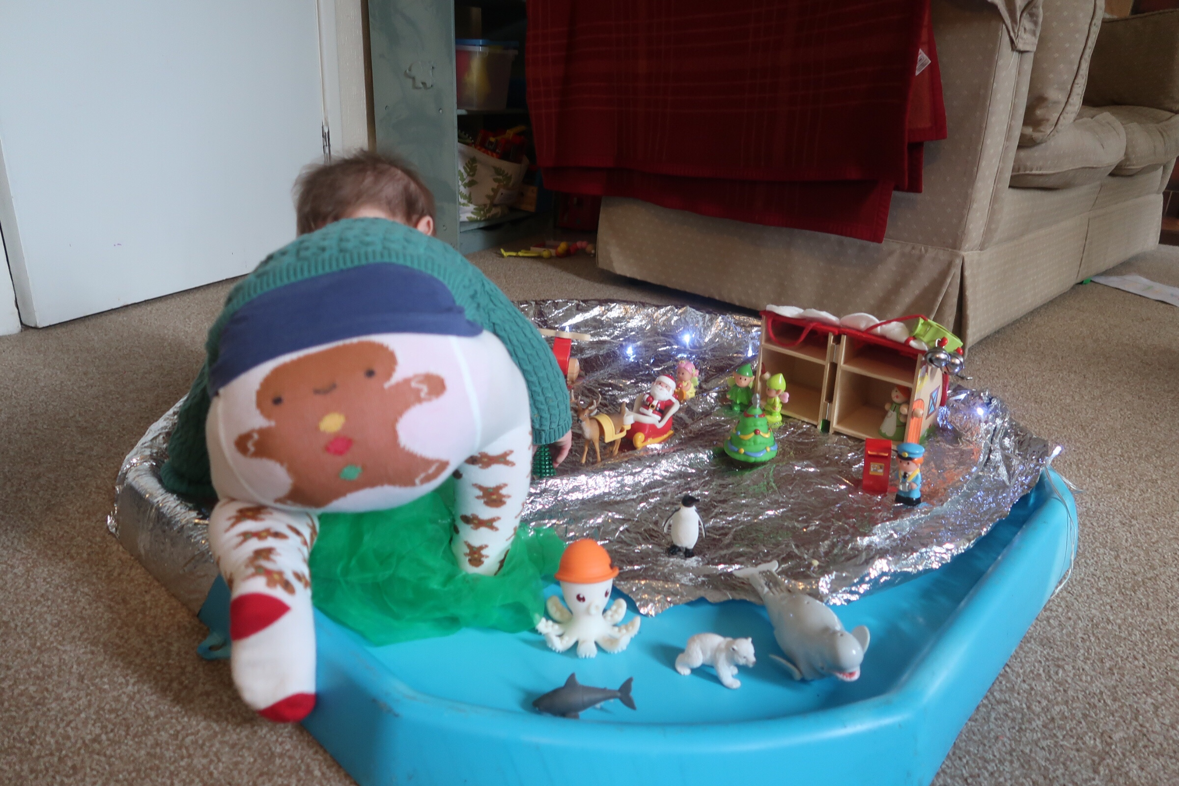 baby playing with small world in a tuff tray.