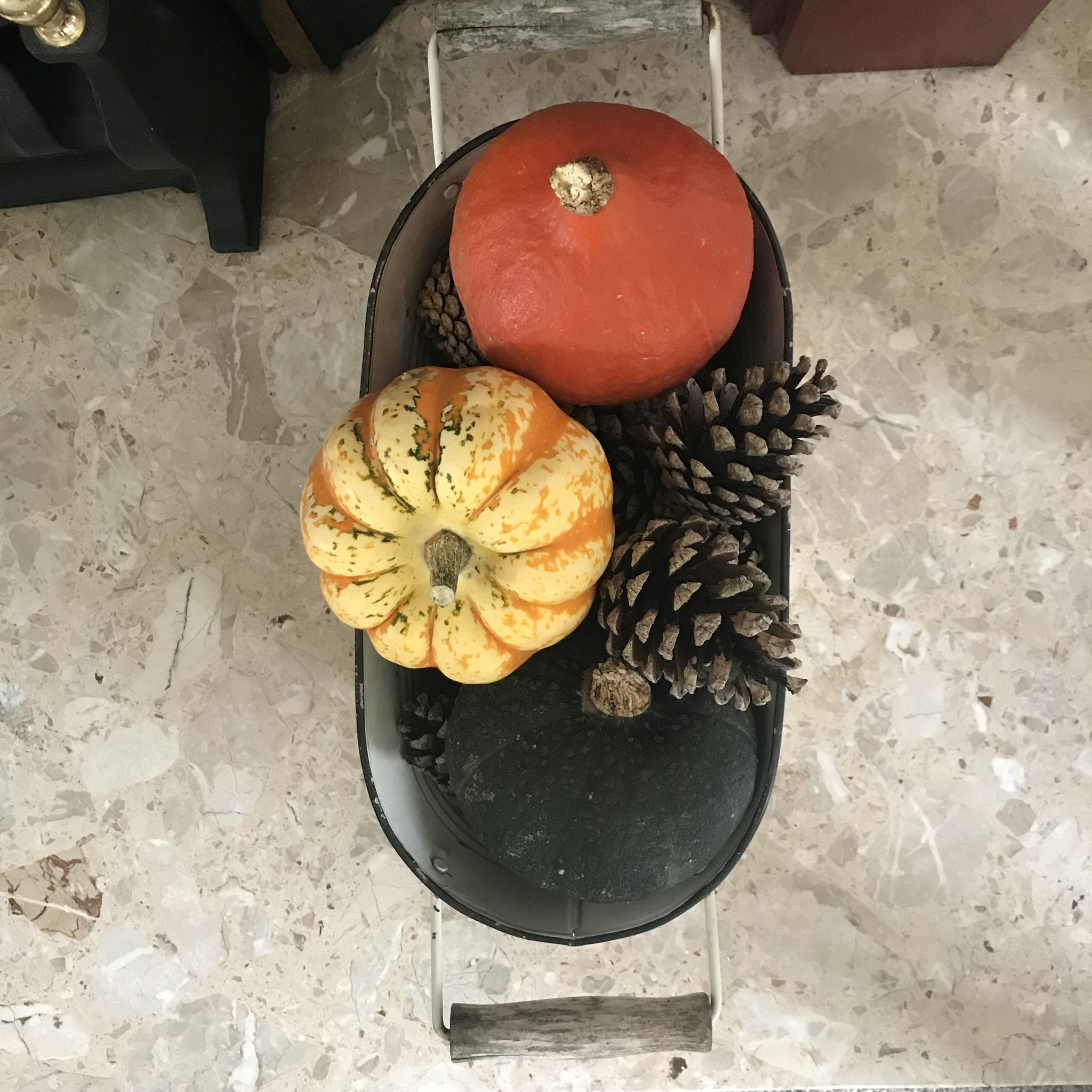 a pot with pumpkins and cones in it