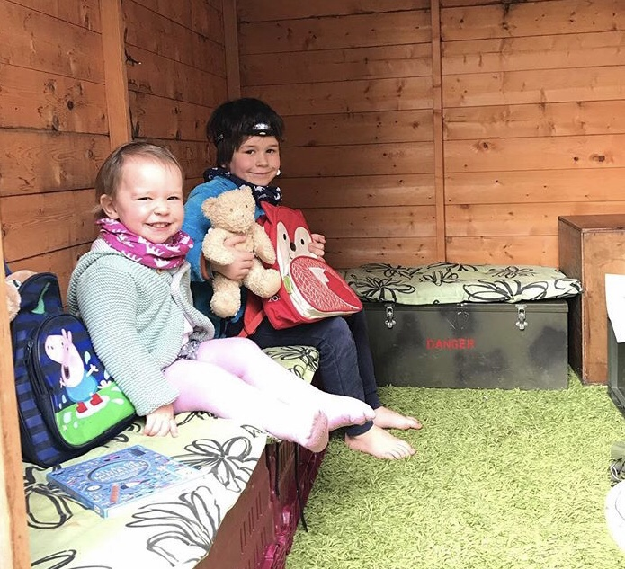 two children on an imaginary expedition in their shed