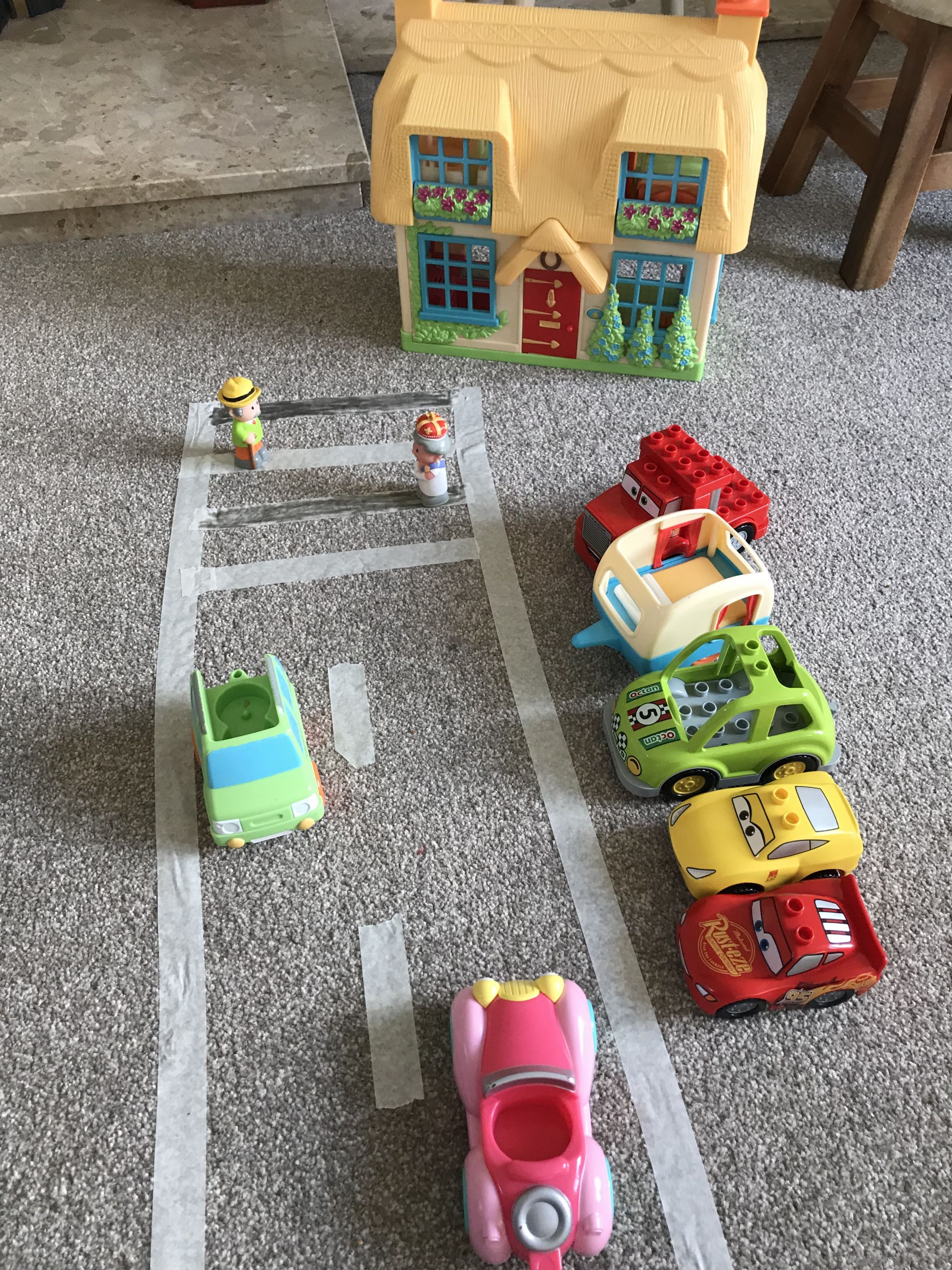 an indoor activity of making a road and village using masking tape and toys