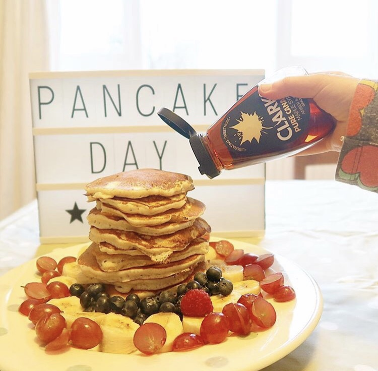 Maple syrup being poured on a star of American pancakes.