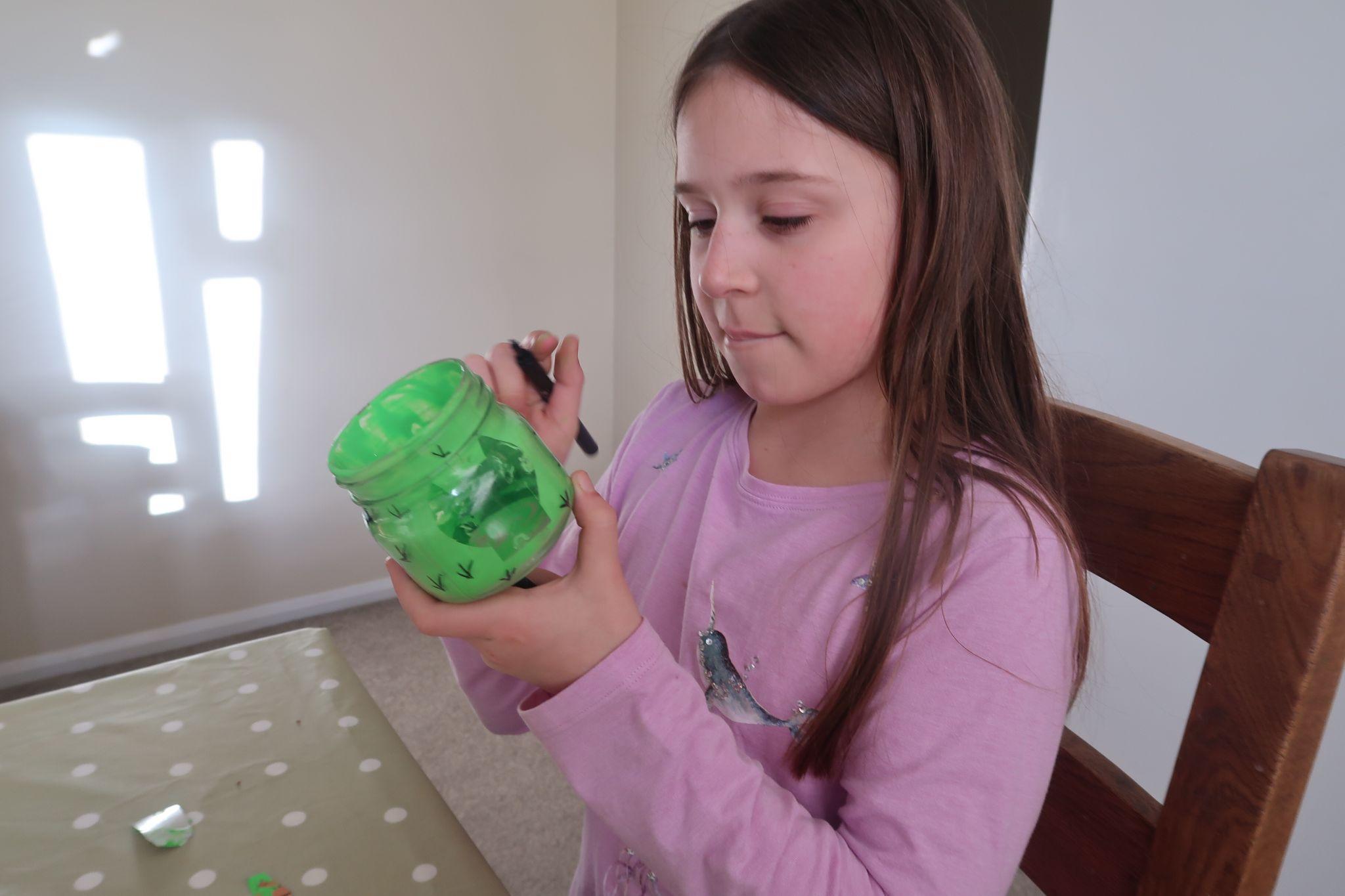girl making cacti marks on glass jar