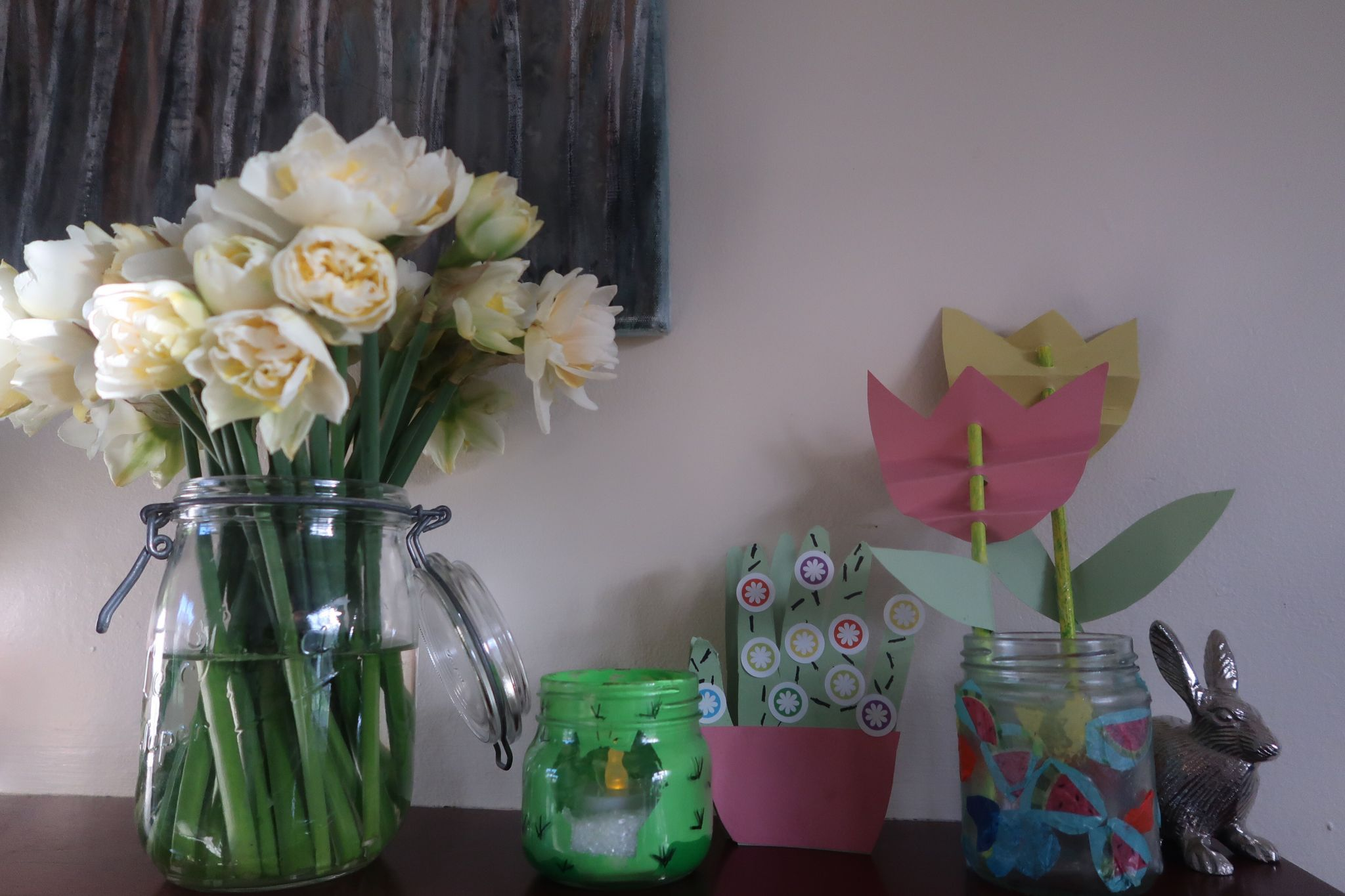 Vase of daffodils sat next to a homemade cacti card, tulip card and homemade jar lanterns.