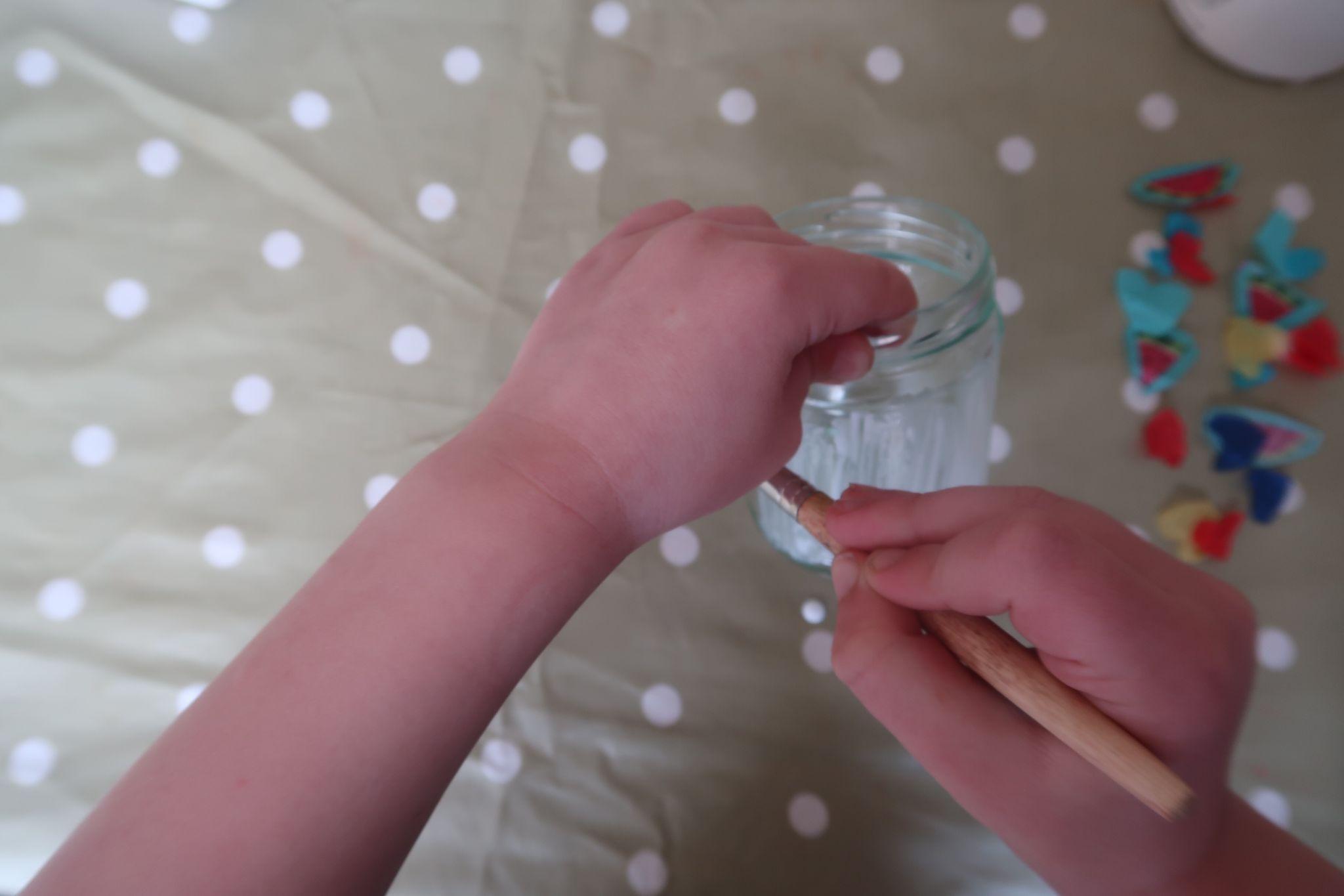 child painting glue on jar