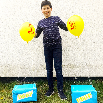 Boy with Fortnite supply boxes with yellow balloons
