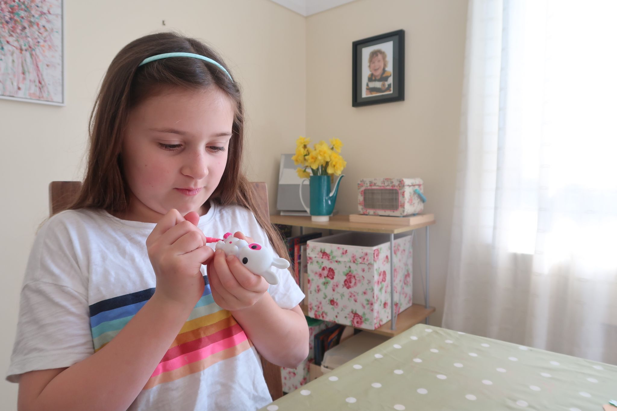 A girl painting a bunny figurine
