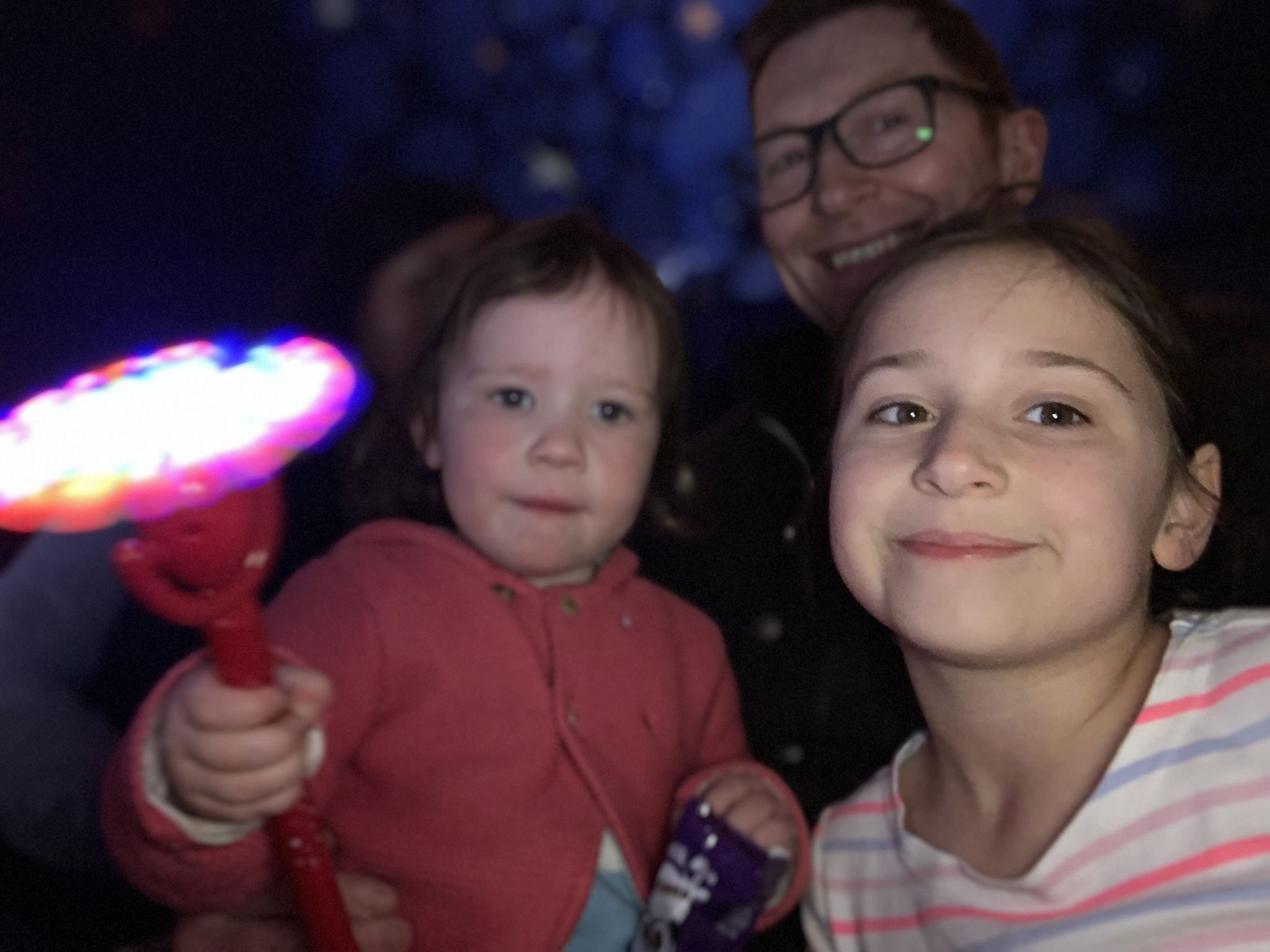 2 children and a dad enjoying watching a circus