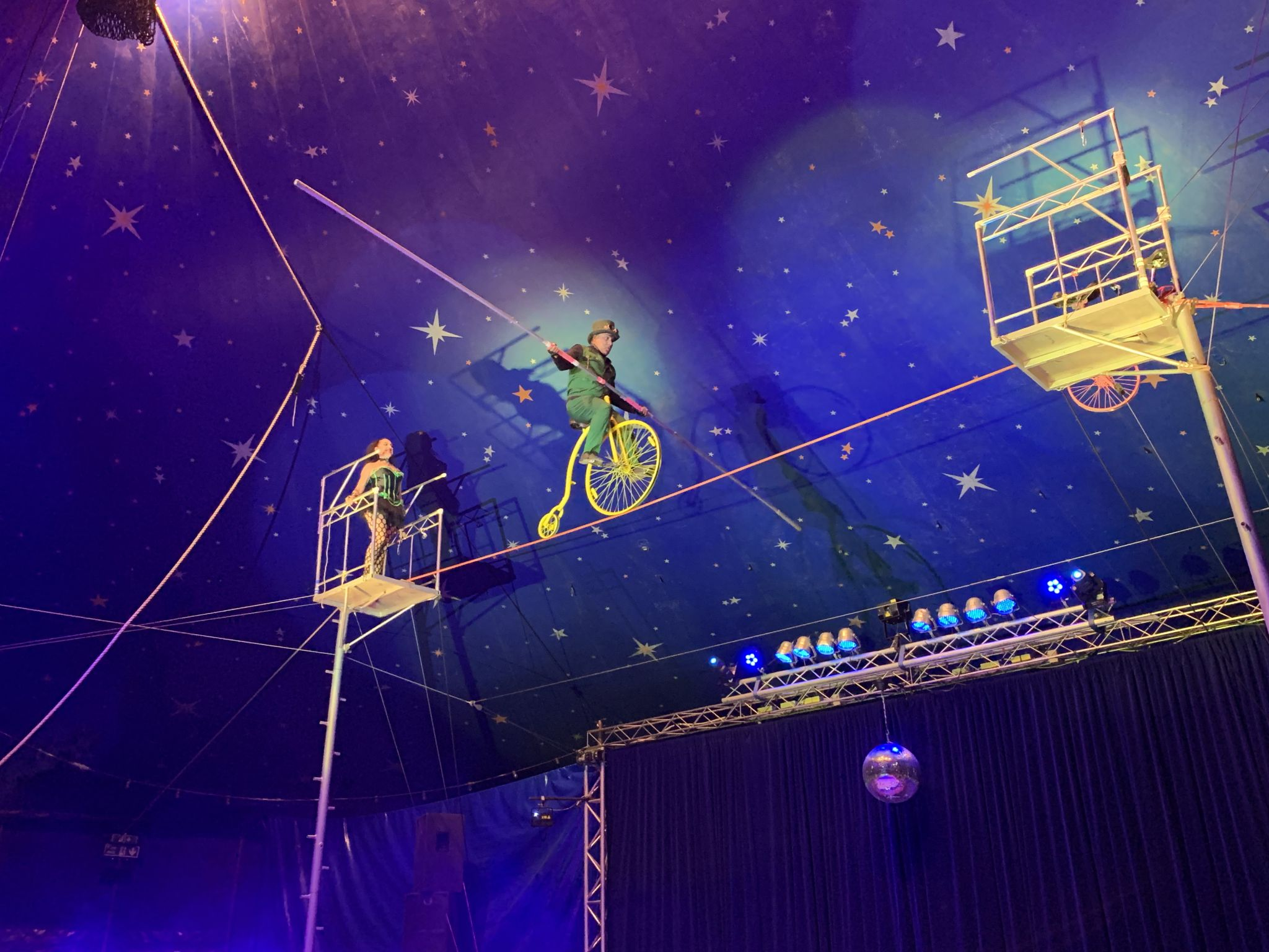 A circus performer riding a unicycle on a tightrope