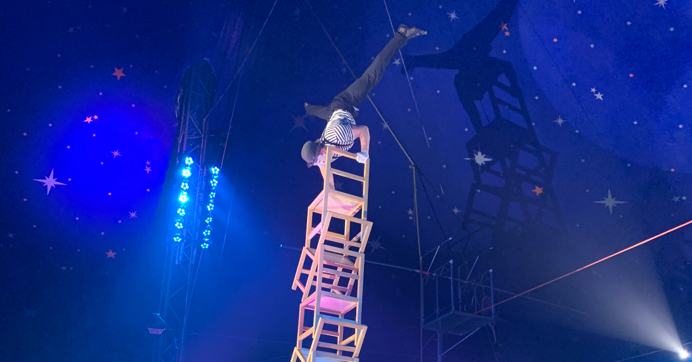 circus performer balancing upside down on chairs