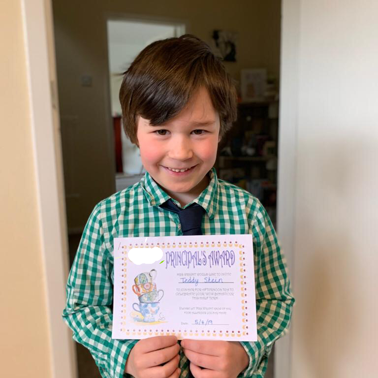 boy in shirt and tie holding a certificate