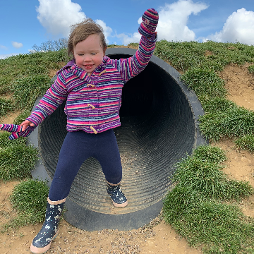 a toddler girl climbing out of a play tunnel
