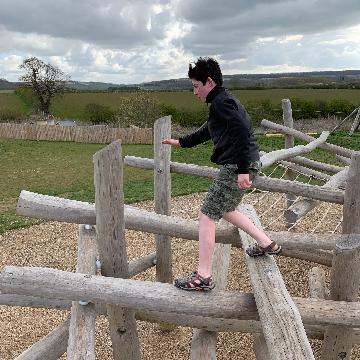 boy climbing on wooden playground