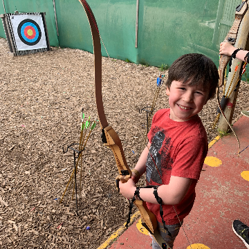 A boy holding a bow and arrow near an archery target
