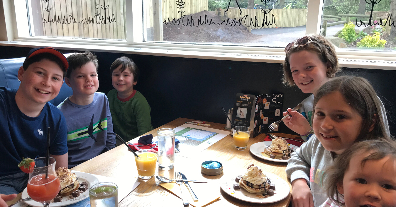 6 children smiling at a cafe serving pancakes