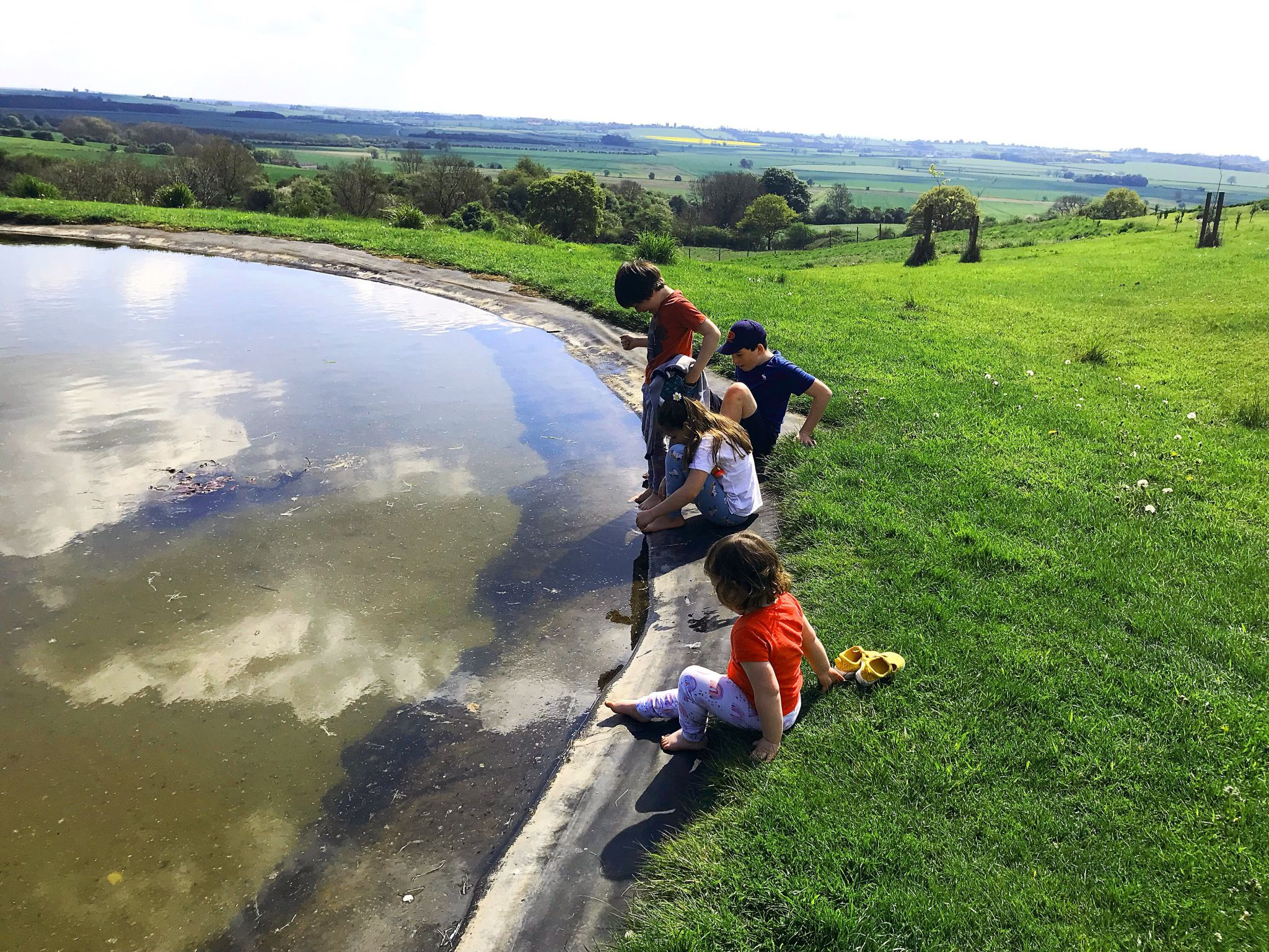four children sat by a pond