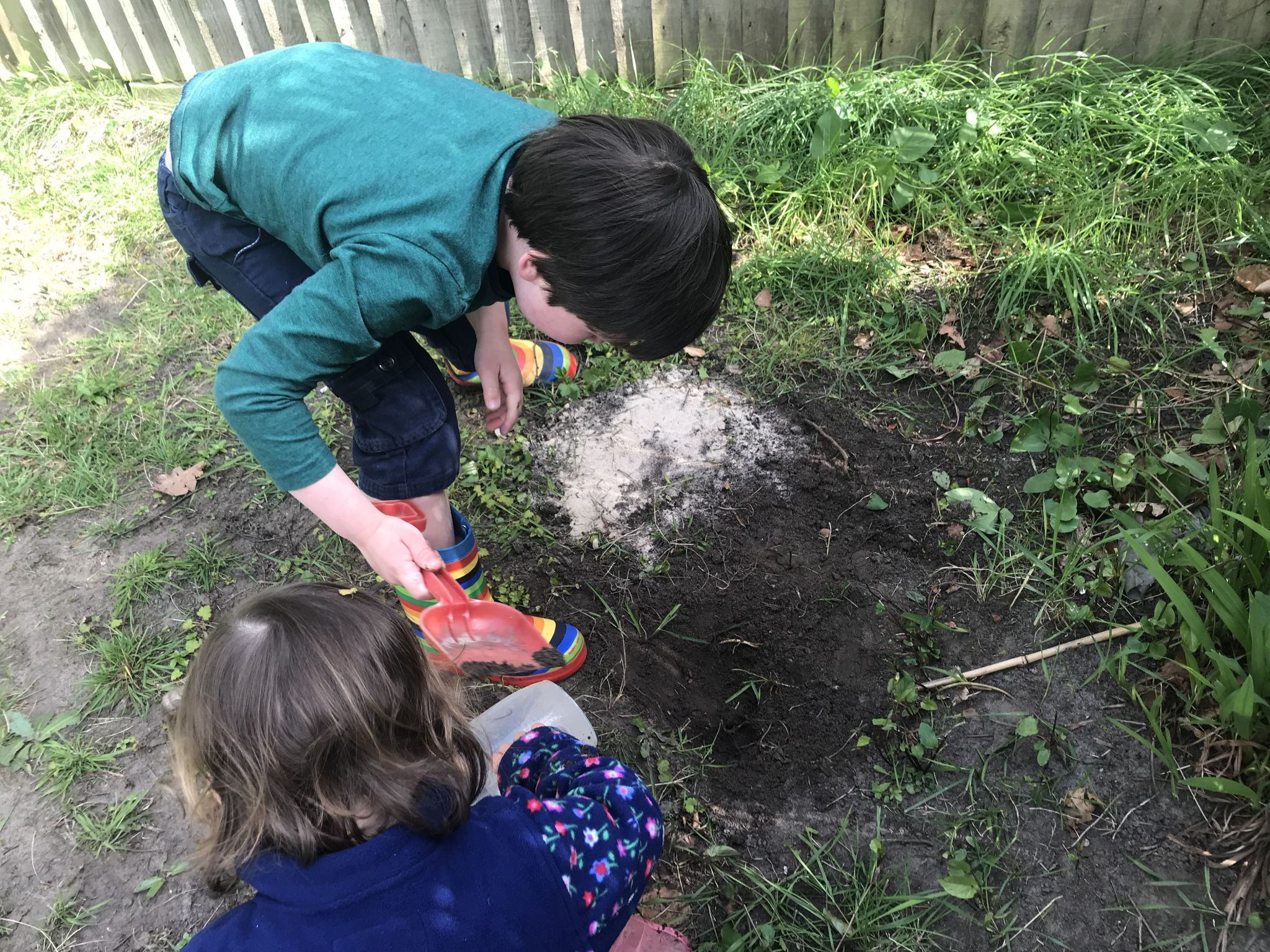 two children digging up the soil