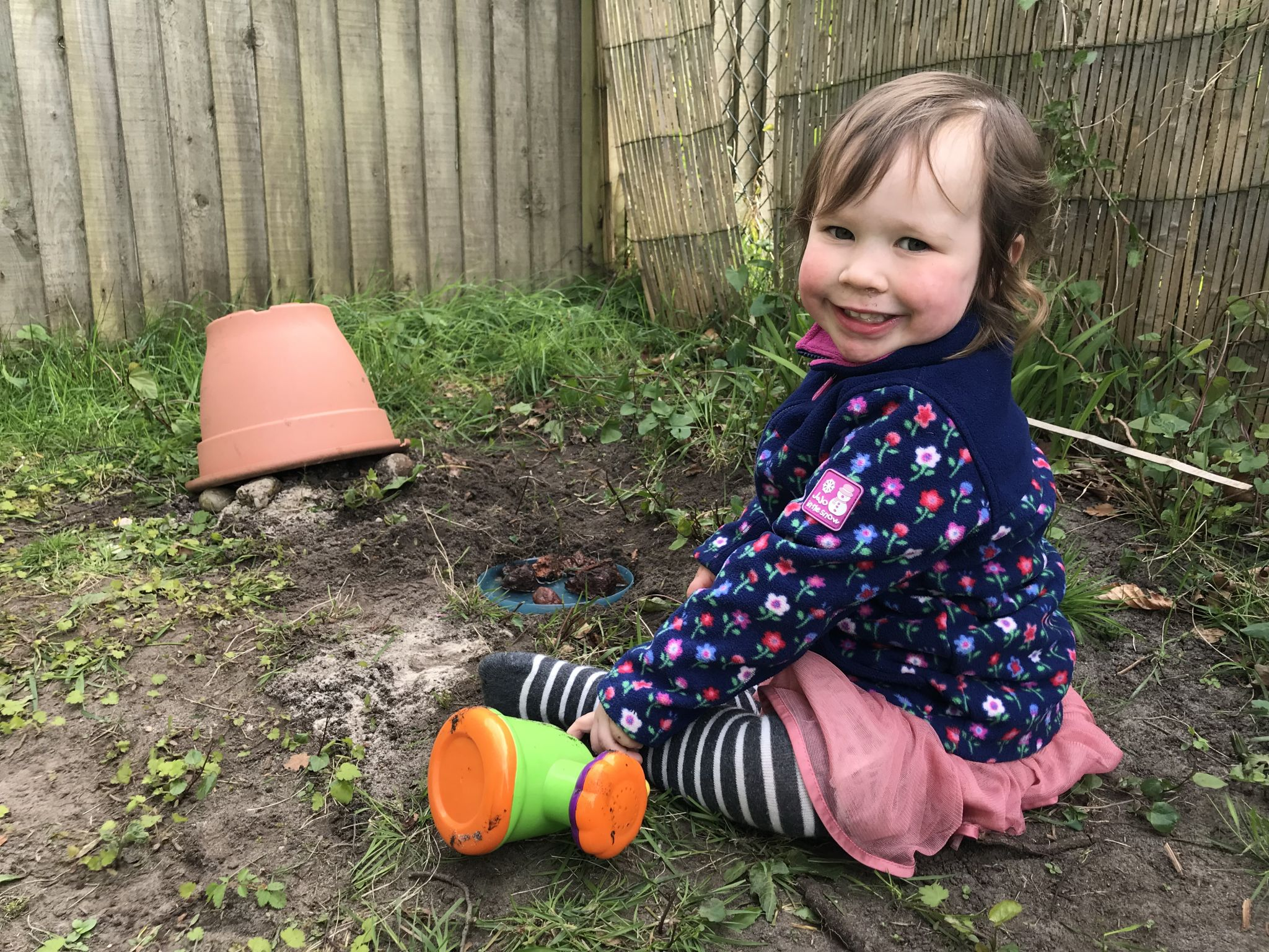 a small child sat in the mud with a homemade toads house out of a pot and rocks