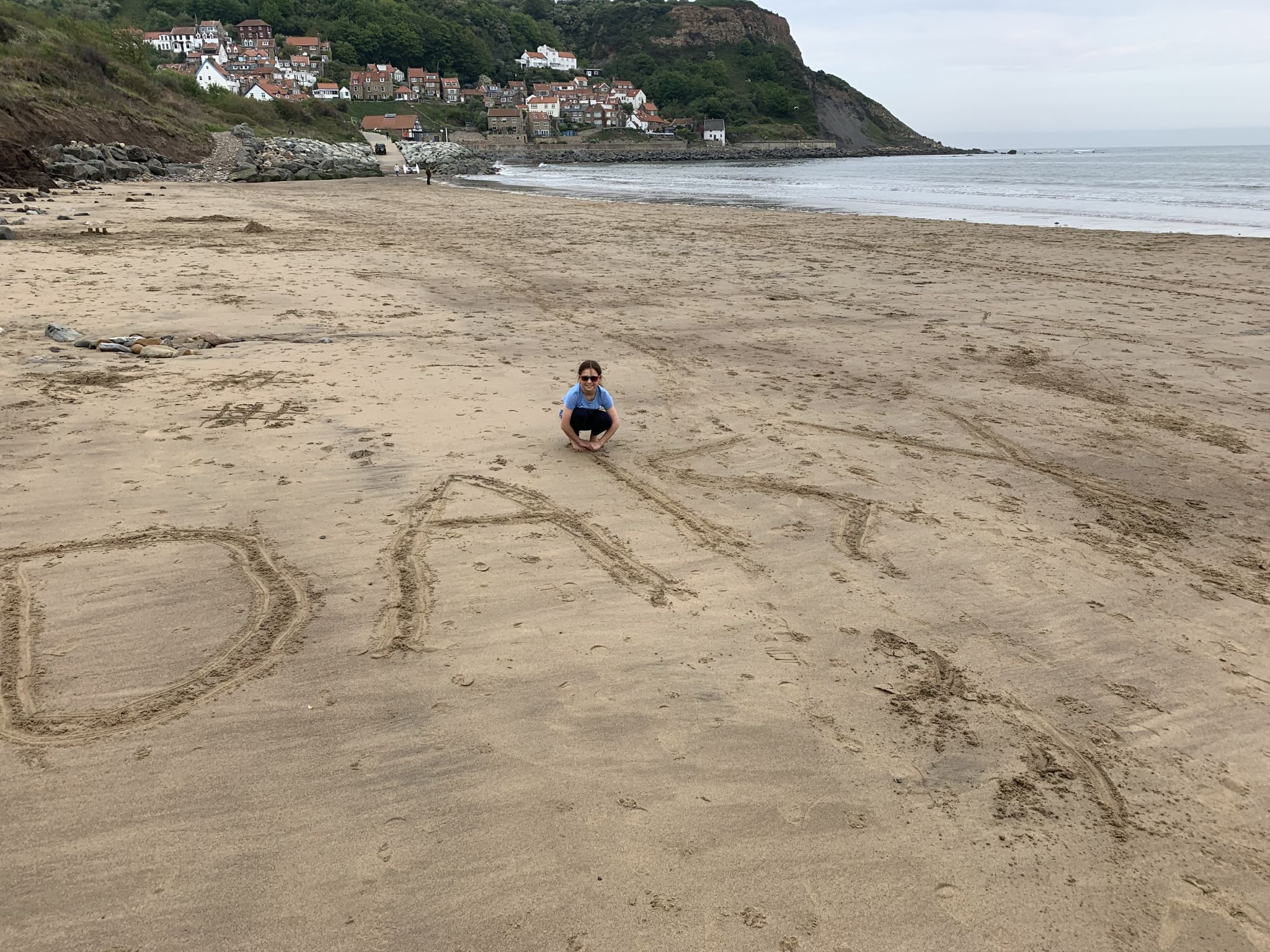 a girl sat on her name written in the sand