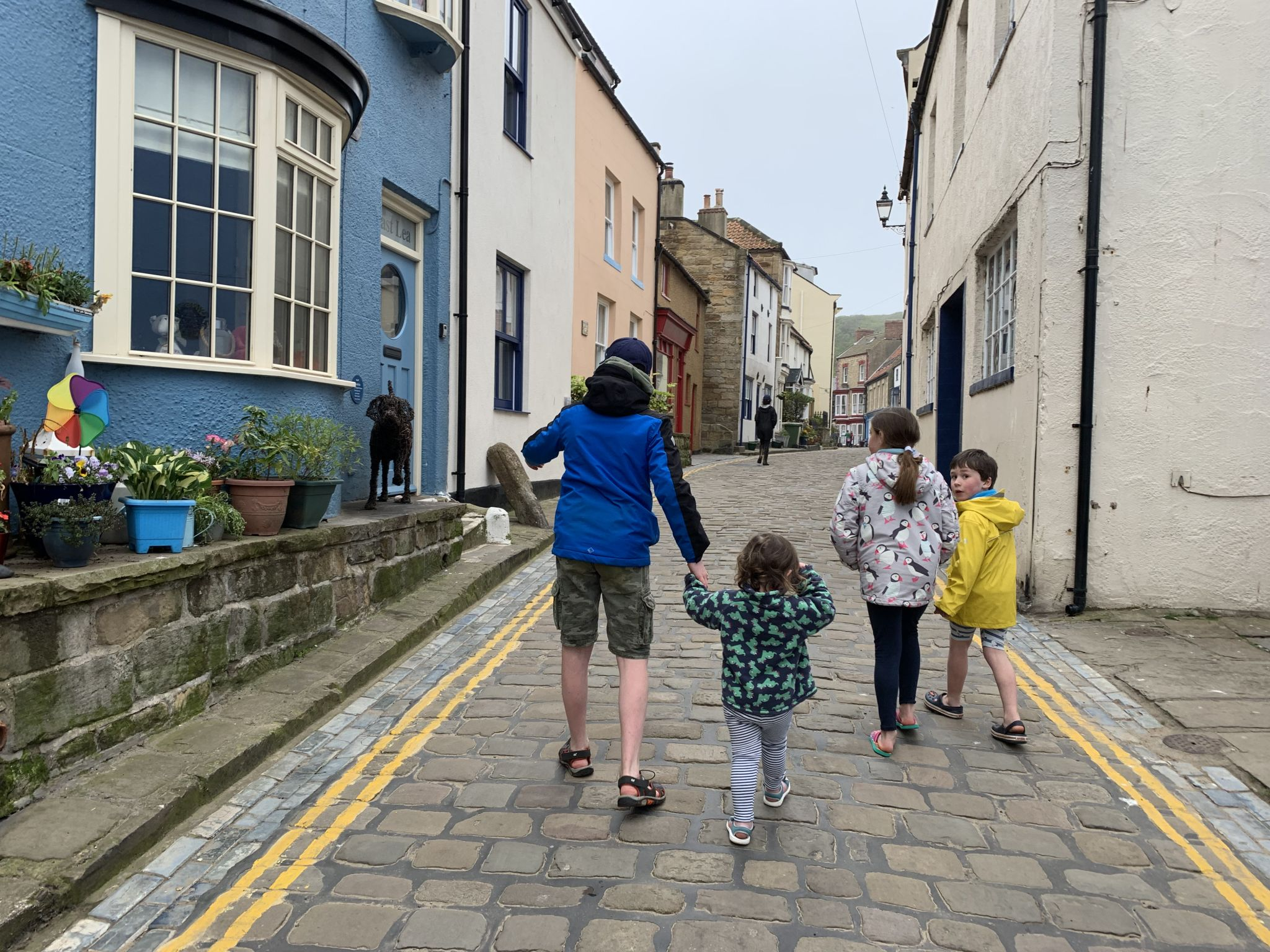 4 children walking up a cobbled street