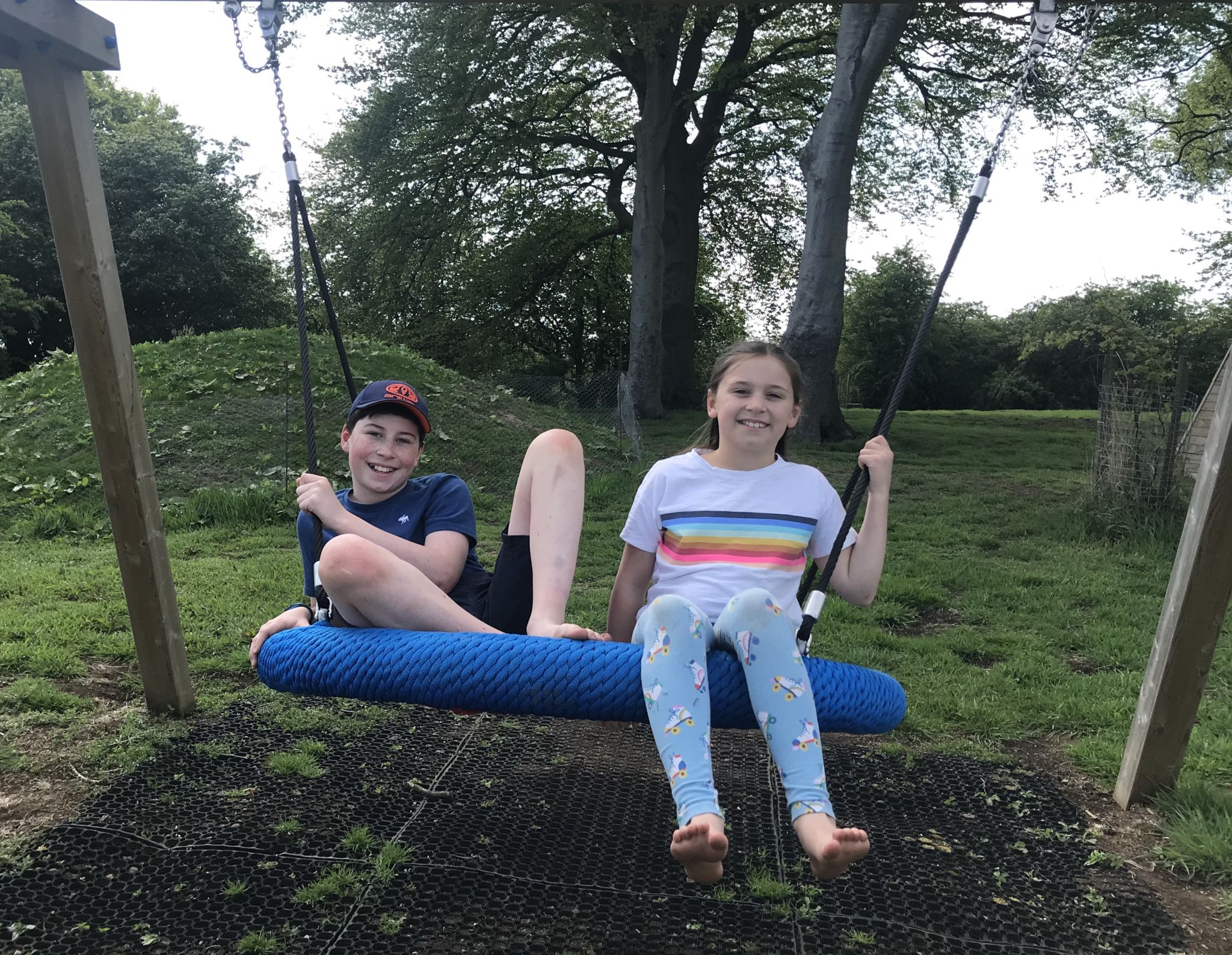 two children sat on a swing