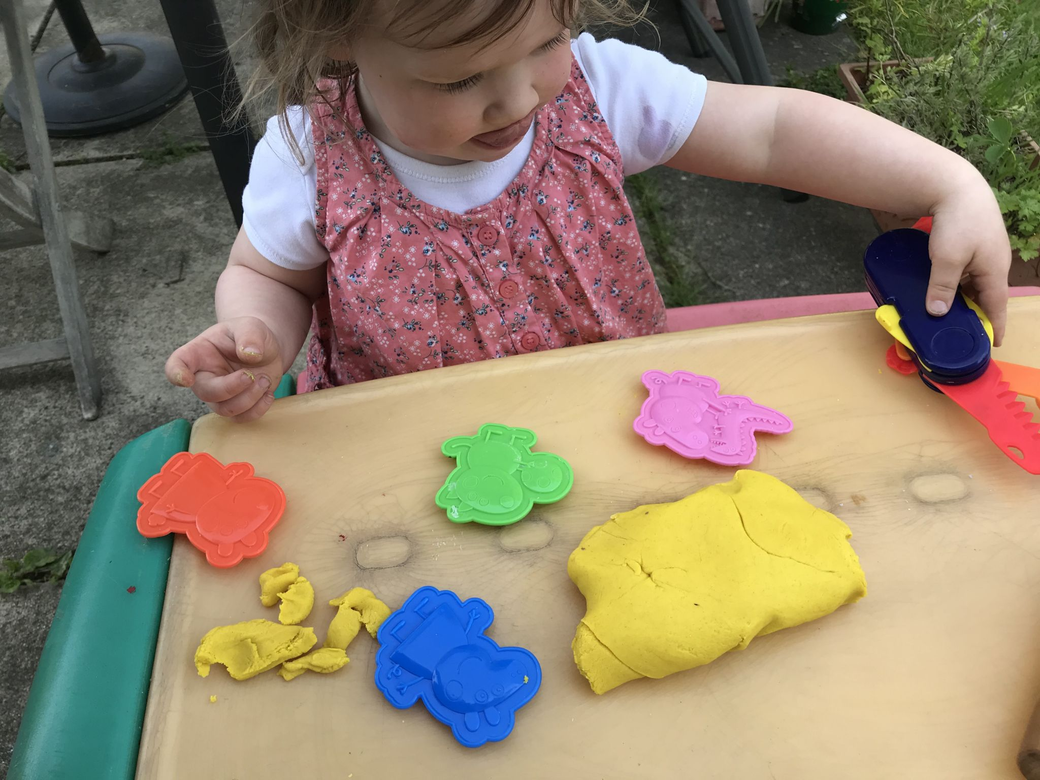toddler sat playing with play dough