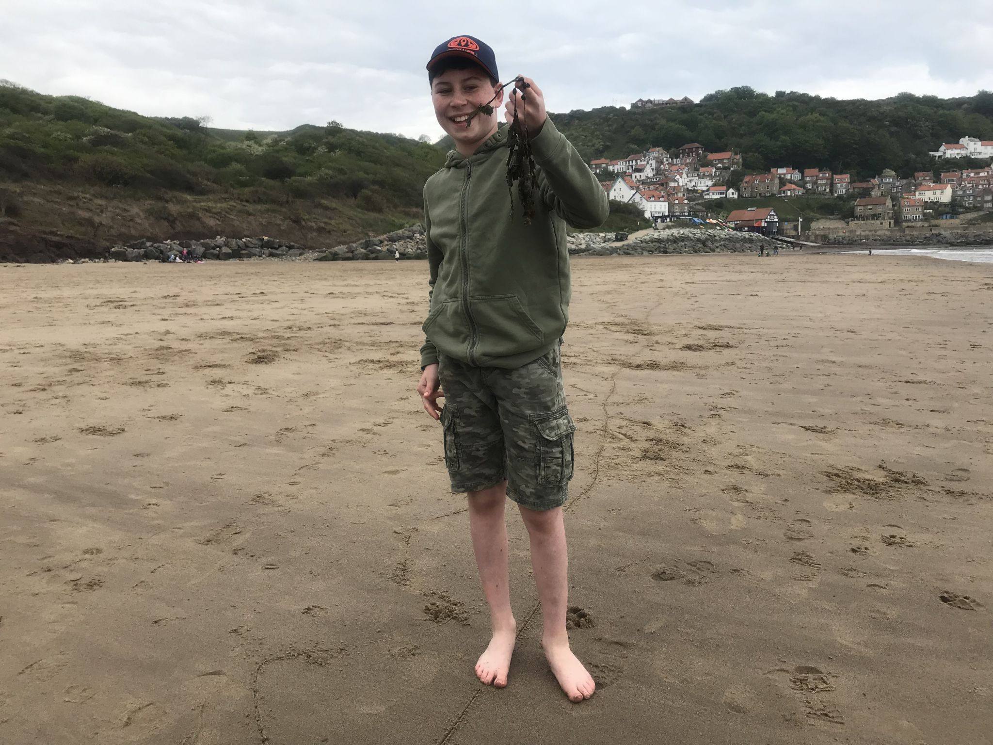 a young teen on the beach holding seaweed