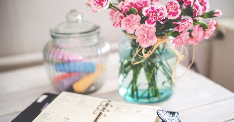 flowers in a jar and chalk in a jar with a diary