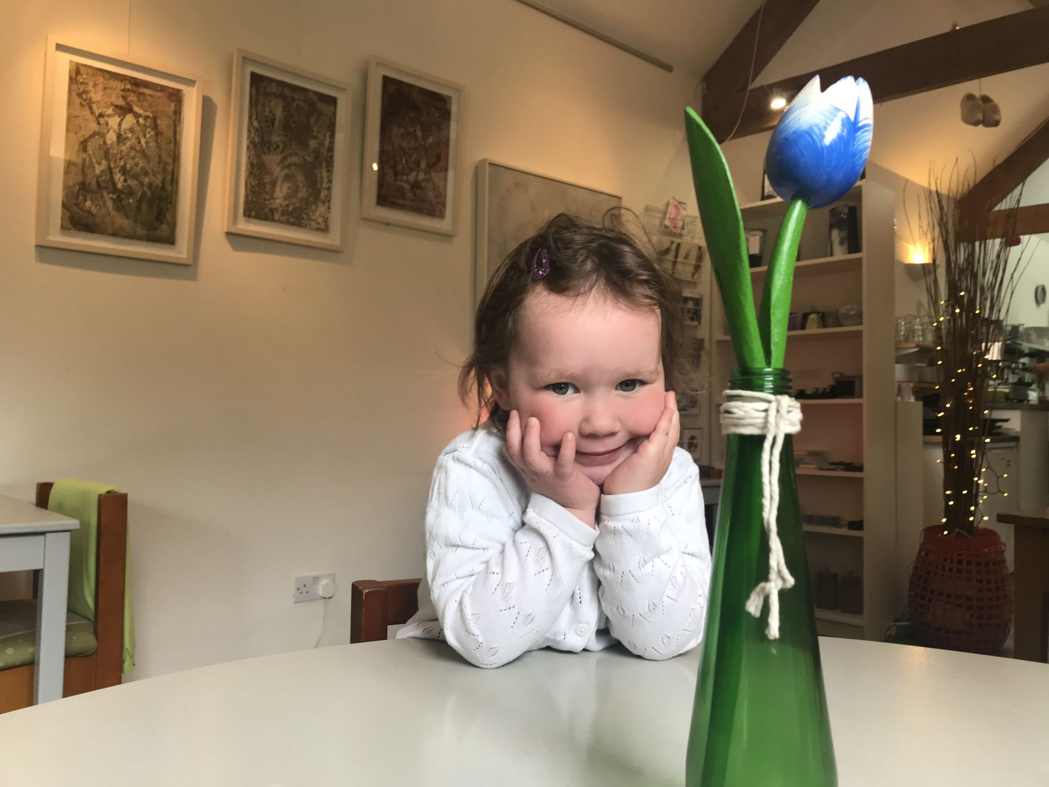 a toddler sat in a cafe posing for a picture with her hands on her chin smiling