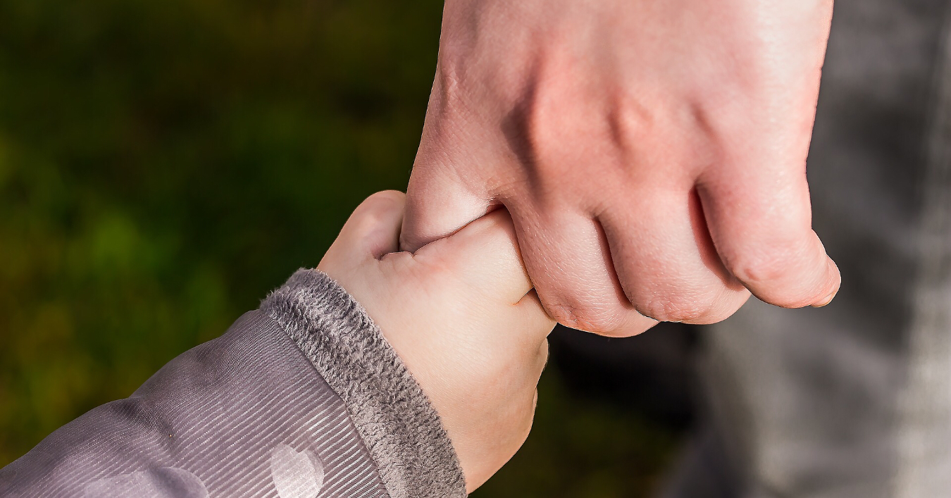 a toddler holding a hand of a parent