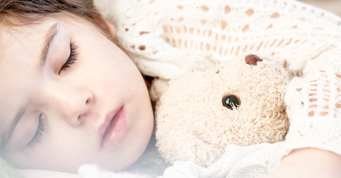 a sleeping toddler holding a bear