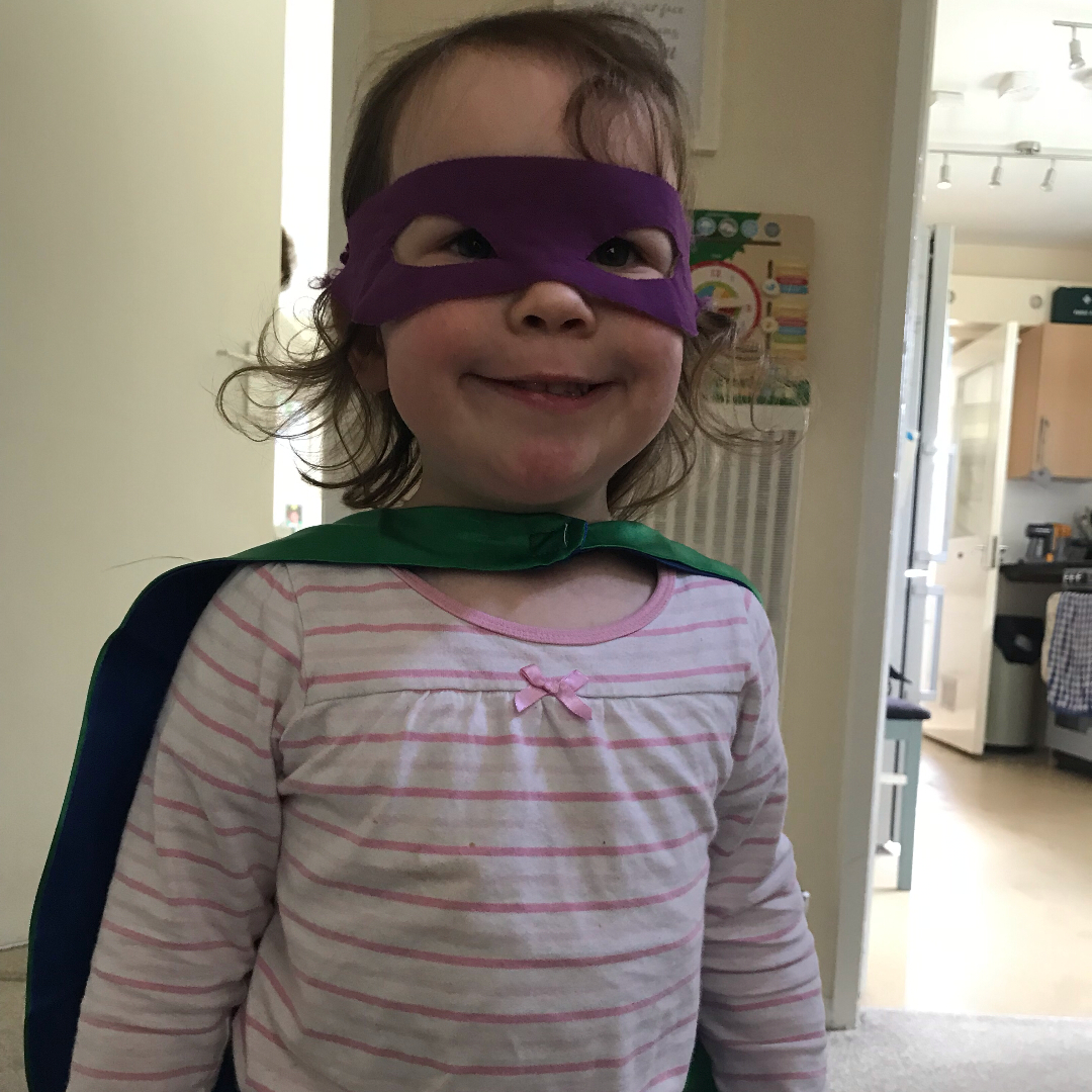 A girl dressed as a superhero with cape and mask