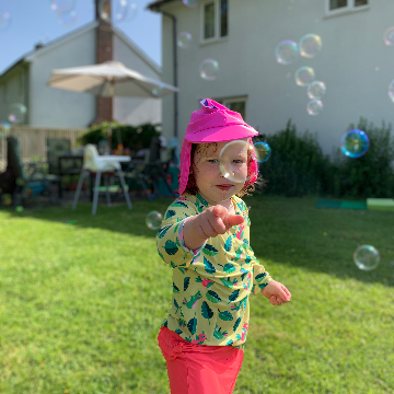 Toddler playing with bubbles in the garden