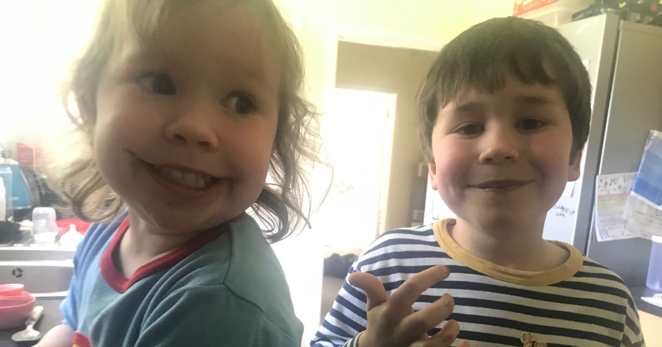 Two young children smiling in the kitchen whilst baking