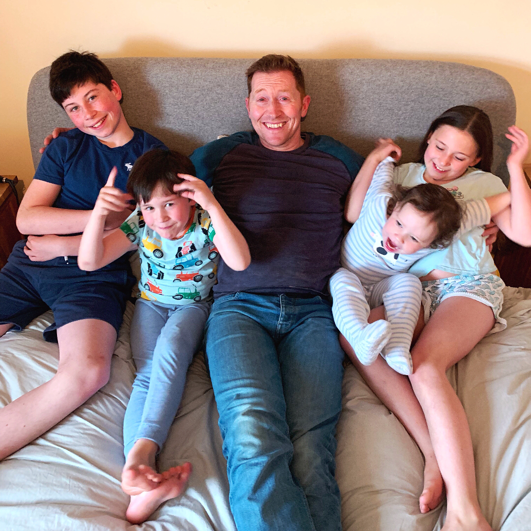a father smiling with his 4 children on a bed