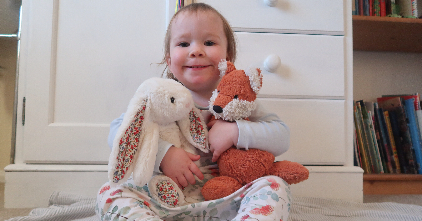a toddler girl hugging a cuddly toy fox and bunny