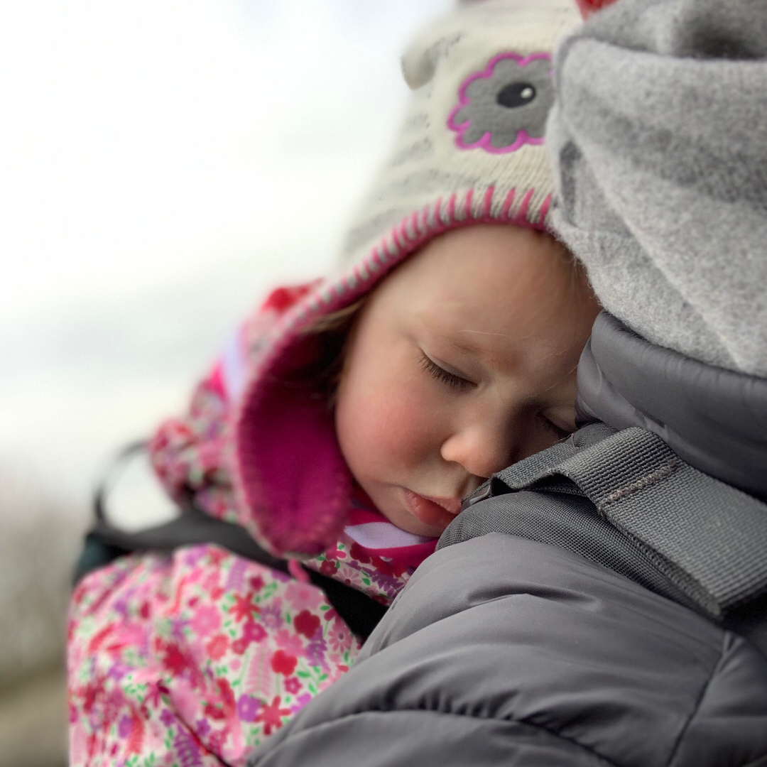 A toddler sleeping outside in a baby carrier