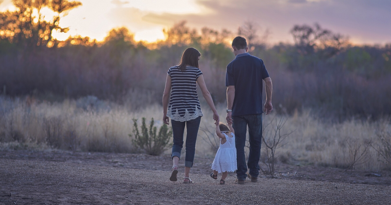 parents walking with a small child into the sunset