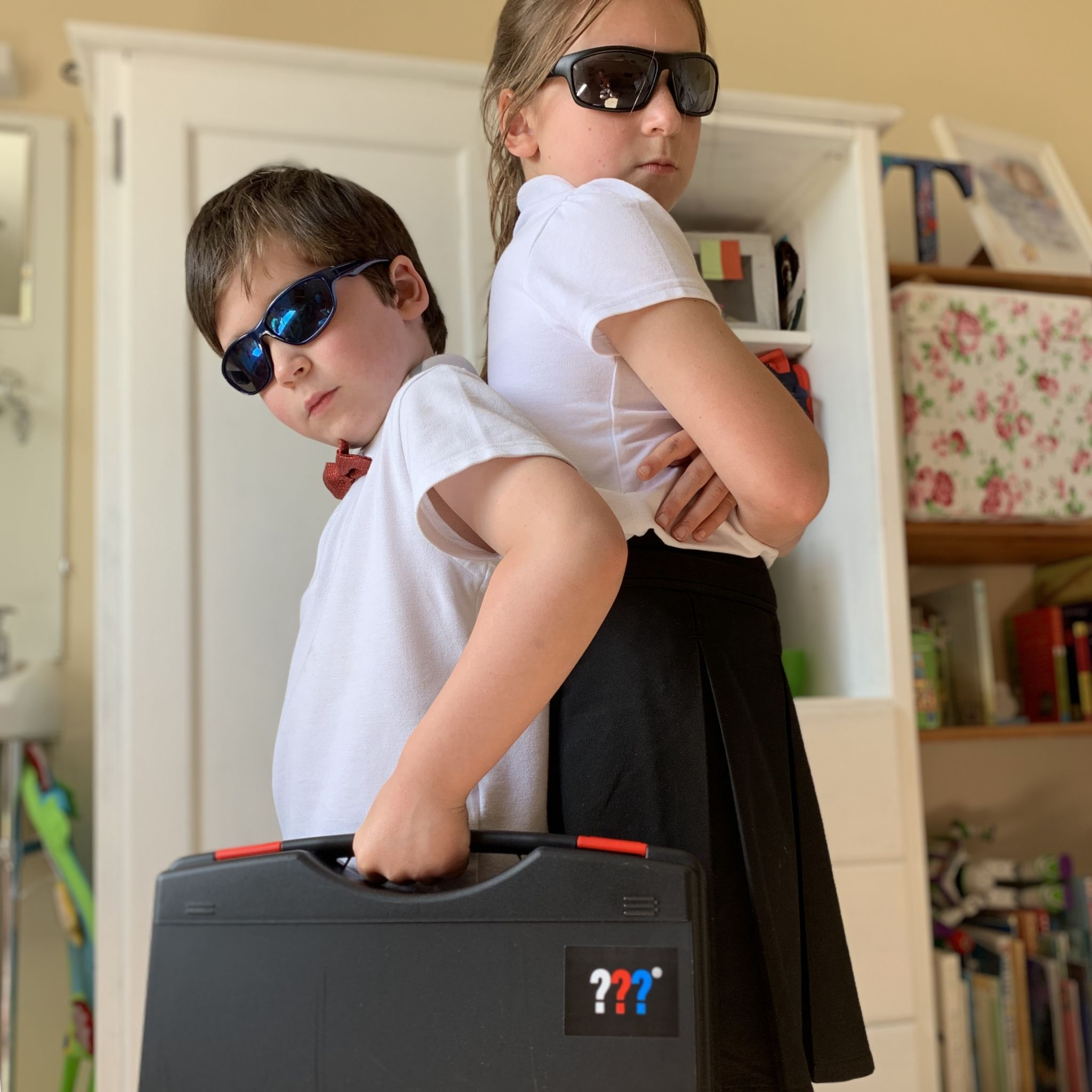 two children in black sunglasses holding a spy case