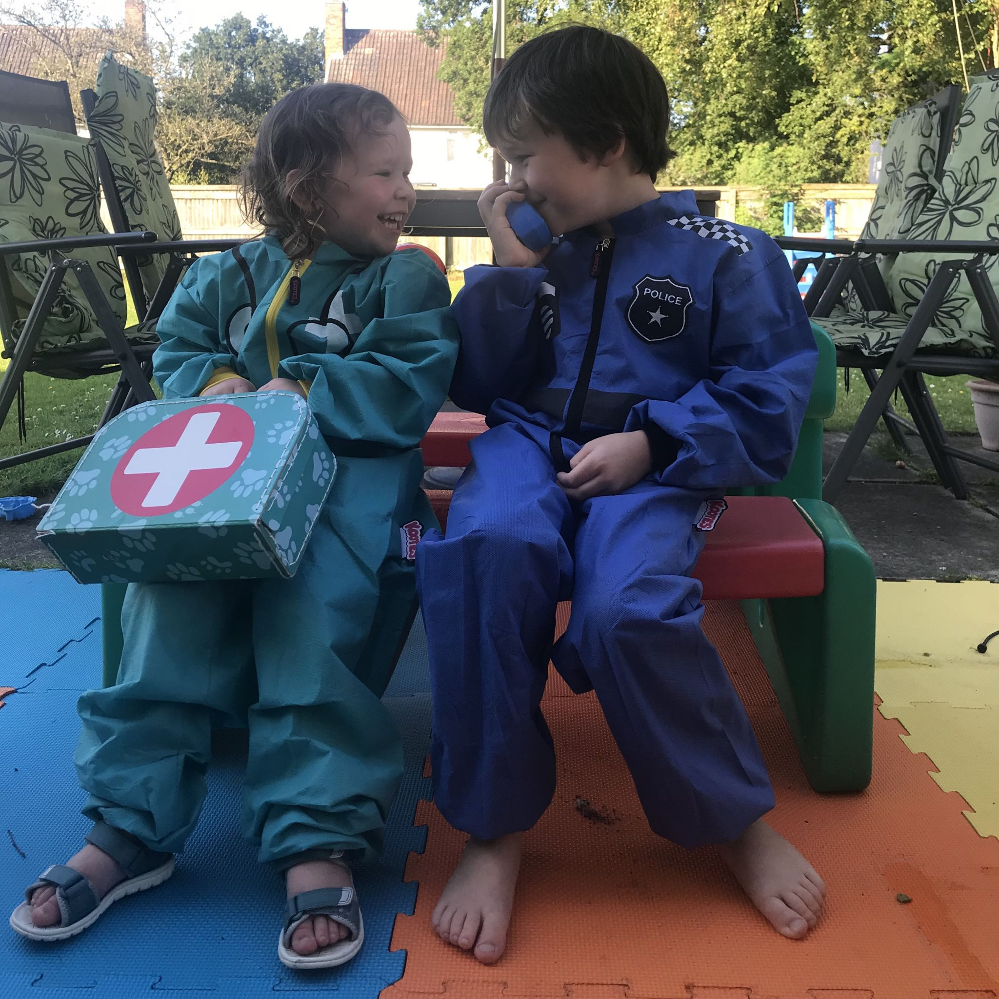 Two children sat down laughing at each other wearing play overalls