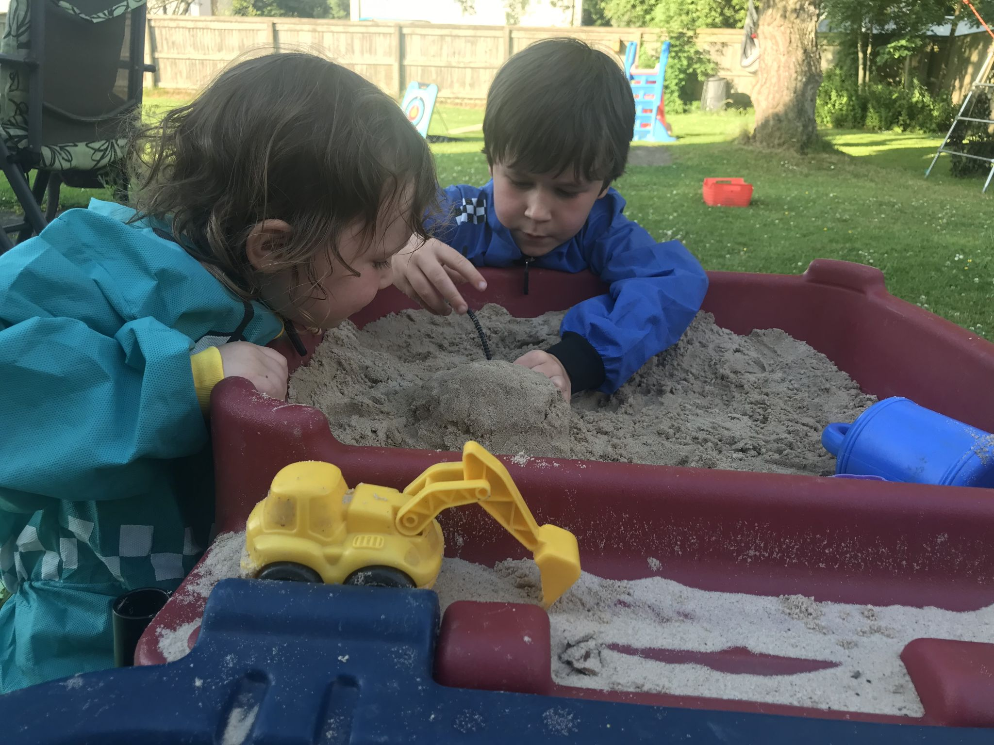 two children playing in a sand table