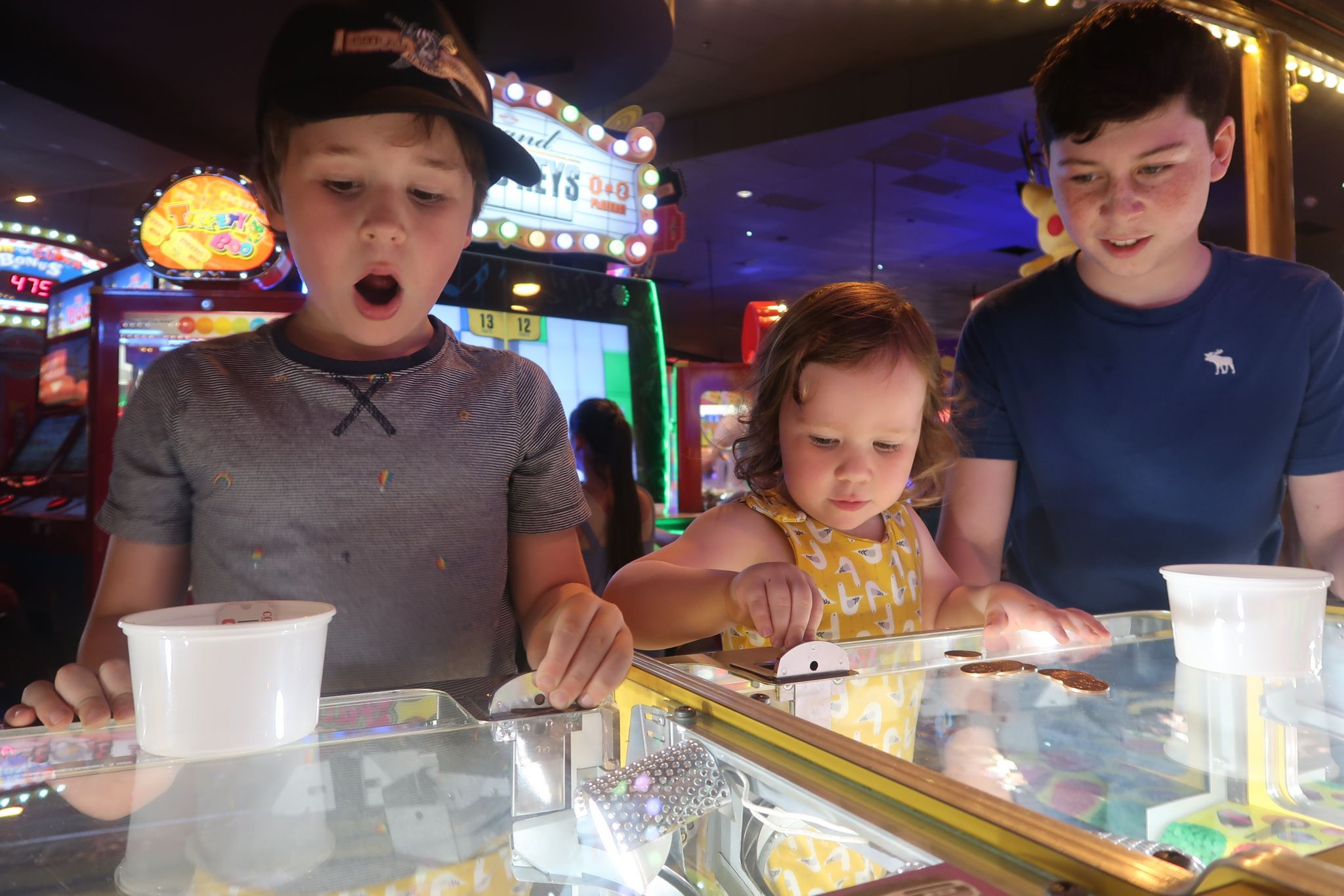 Three kids playing the 2p slot machines