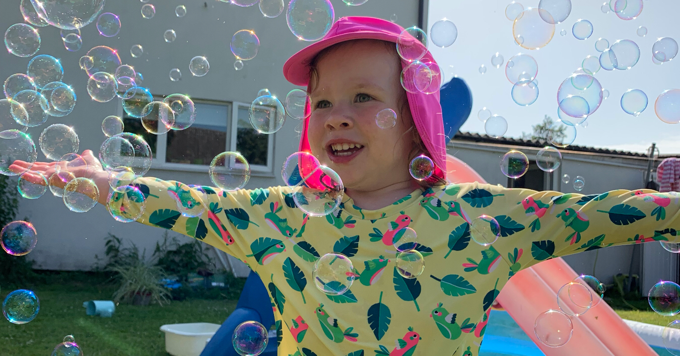 A girl playing in the garden with bubbles