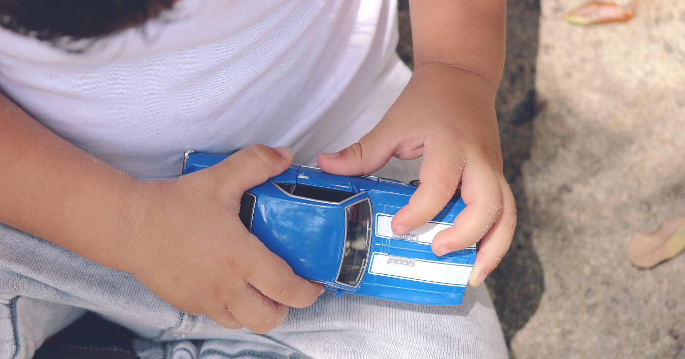 Child playing with a small car
