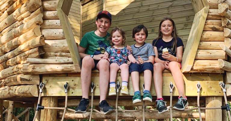 4 children in a wooden park sat together