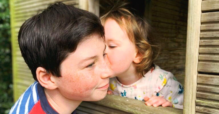 a toddler kissing her brother