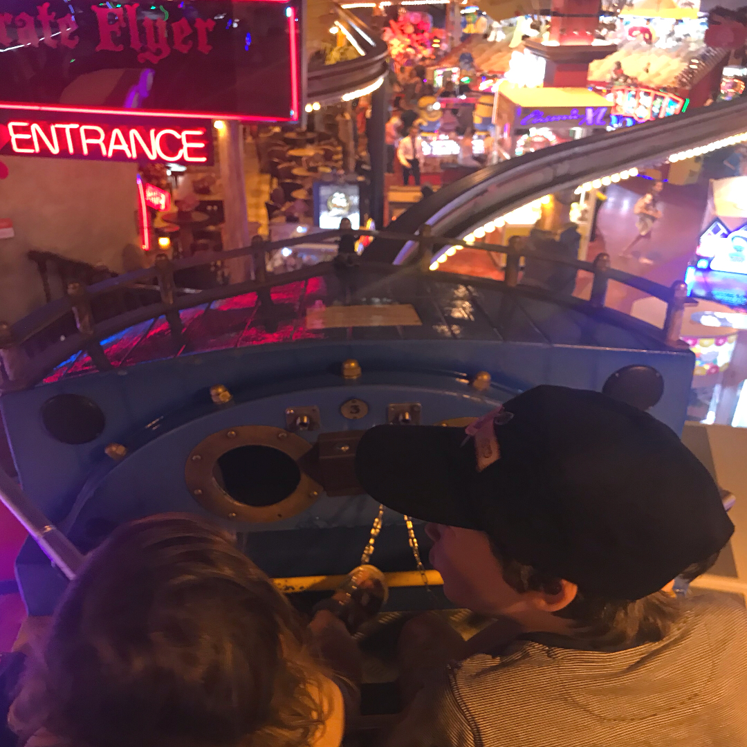 2 children on a monorail ride in an arcade