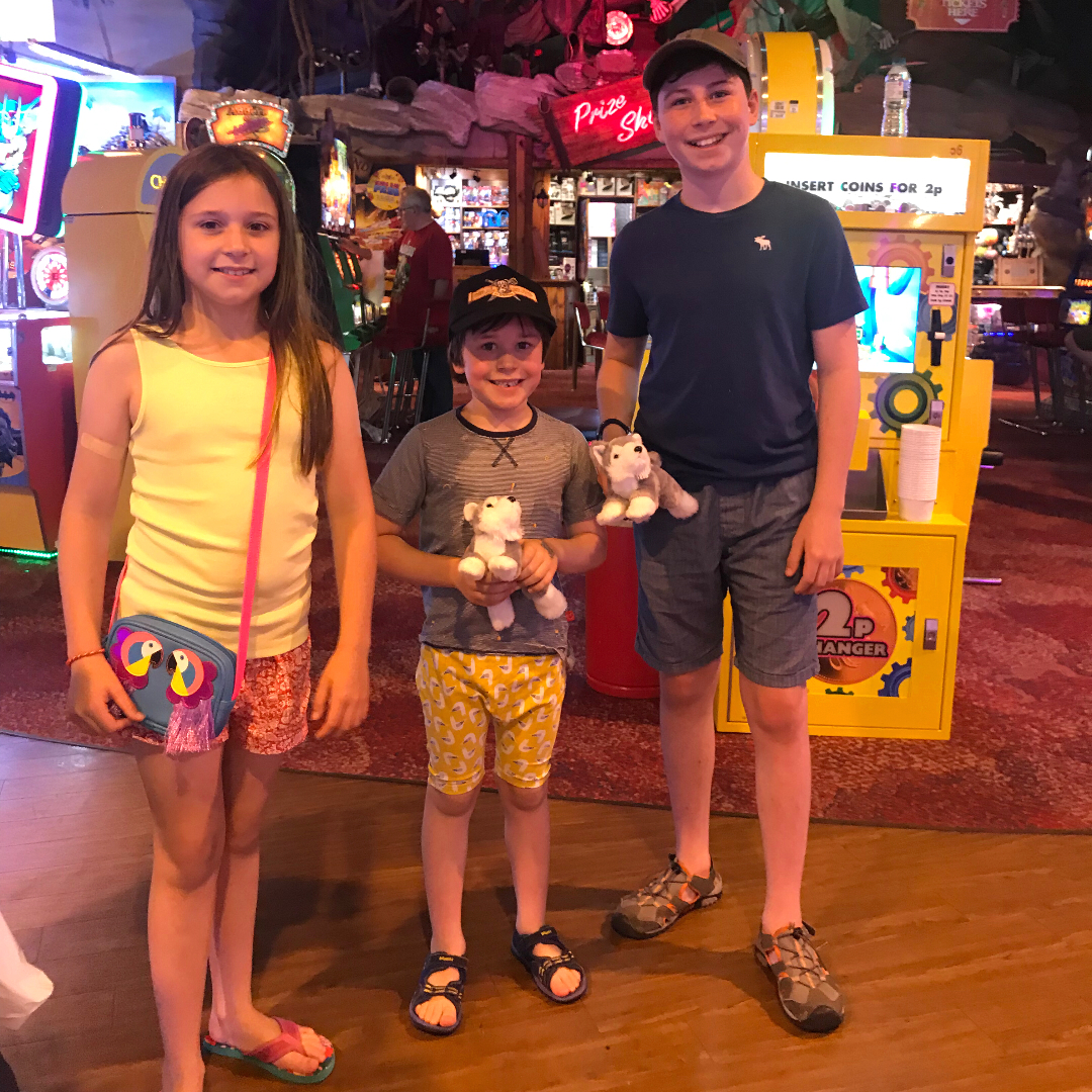 Three children posing for a photo in an arcade